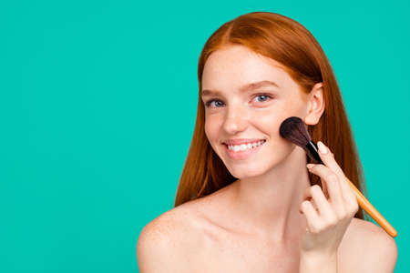 Foto de Advertising concept. Portrait of nice charming positive nude red-haired girl with shiny pure clean fresh smooth flawless skin with healthy tone, doing makeup with brush, on green turquoise background - Imagen libre de derechos