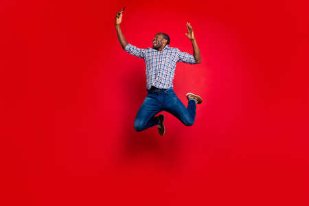 Photo pour Full length body size of nice funny crazy handsome attractive cheerful cheery positive guy wearing checkered shirt holding in hands cell reading text isolated over bright vivid shine red background - image libre de droit