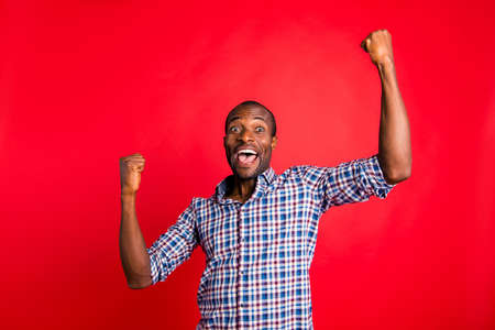 Photo pour Portrait of handsome cheerful glad optimistic positive guy wearing checked shirt showing fortunate winning gesture holding fists raising hands up isolated over bright vivid shine red background - image libre de droit