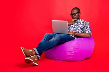 Foto de Nice calm focused concentrated handsome guy wearing checked shirt working remotely on laptop creating presentation sitting on violet bag isolated over bright vivid shine red background - Imagen libre de derechos