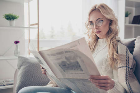 Photo pour Portrait of nice adorable attractive intelligent wavy-haired lady housewife wearing sweater holding in hands reading interesting digest in light interior room - image libre de droit