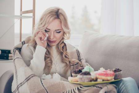 Photo for Portrait of broken heart dumped by boyfriend girlfriend gloomy worried wavy-haired lady on divan crying big large plate of tempting seductive homemade baked sweets in light interior room - Royalty Free Image