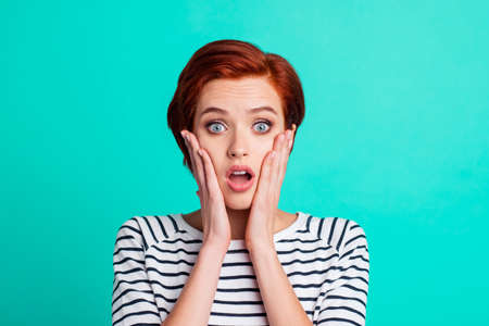 Photo pour Close-up portrait of nice charming attractive lovely pretty shocked red-haired lady in striped pullover palms on cheeks isolated over bright vivid shine green turquoise background - image libre de droit