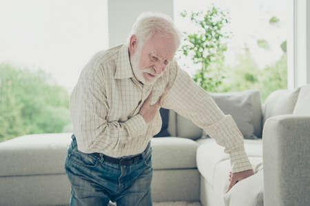 Foto de Sad tired stylish old man wearing checked shirt leaning on divan - Imagen libre de derechos
