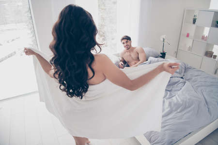 Photo pour A woman in white towel flashing her body to her husband lying on the bed. rear view - image libre de droit