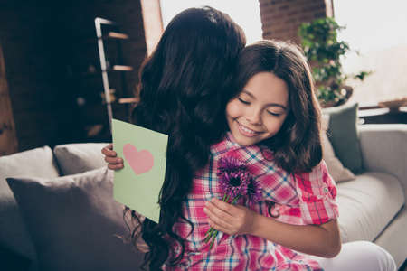 Photo for Close up back behind rear view photo two people hug mum little daughter eyes closed bouquet postcard present heart melting wear pink plaid shirts flat apartment room sit cozy couch sofa divan - Royalty Free Image