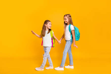 Foto de Full length body size view of two nice attractive cheerful smart clever pre-teen girls with colorful backpacks holding hands back to school isolated over bright vivid shine yellow background - Imagen libre de derechos
