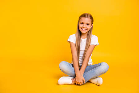Foto de Portrait of her she nice cute sweet attractive cheerful straight-haired pre-teen girl sitting in lotus pose isolated over bright vivid shine yellow background - Imagen libre de derechos
