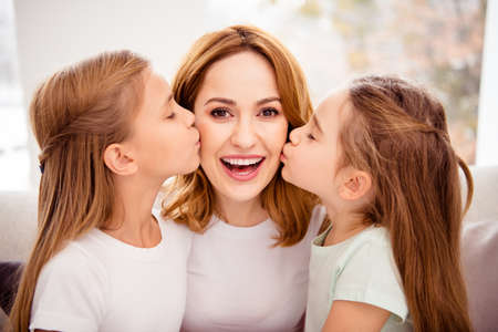 Photo pour Close-up portrait of nice cute lovely winsome sweet gentle tender attractive charming cheerful cheery positive glad redhair people mom kissing pre-teen girls in house indoors - image libre de droit