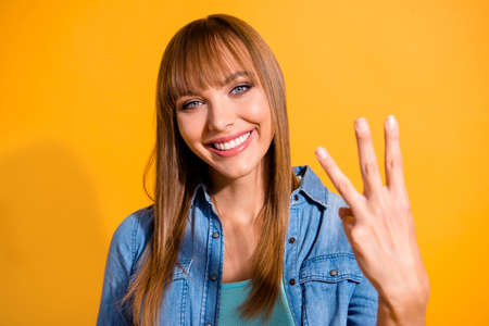 Foto de Close-up portrait of her she nice cute sweet lovely winsome fascinating attractive cheerful straight-haired lady showing 3 middle fingers isolated over bright vivid shine yellow background - Imagen libre de derechos