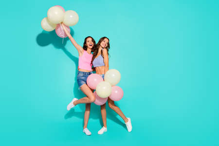 Foto de Full length body size photo funny beautiful amazing two she her ladies colored balloons hands arms raised skinny legs wearing shiny jeans denim shorts tank tops isolated teal bright vivid background - Imagen libre de derechos