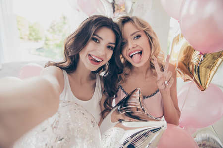 Foto de Close up portrait amazing beautiful she her ladies sitting bed pink linen sheets make take selfies show v-sign tongue out mouth flirty sleep costumes friends girls day night holiday before marriage - Imagen libre de derechos
