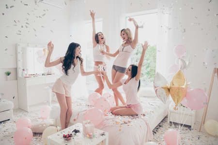 Photo for Nice-looking cool careless carefree attractive feminine charming fit thin slim graceful cheerful funny girlfriends having fun gathering meeting in light white interior decorated house - Royalty Free Image