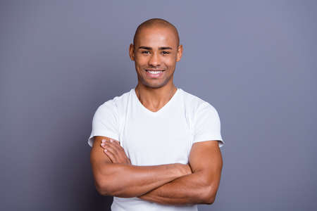 Foto de Close up photo attractive strong healthy masculine dark skin he him his macho bald head arms crossed kindhearted toothy smiling wearing white t-shirt outfit clothes isolated grey background - Imagen libre de derechos