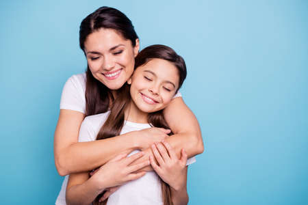 Photo pour Close up photo pretty two people brown haired mum small little daughter stand hugging piggy back lovely close eyes free time rejoice wearing white t-shirts isolated on bright blue background - image libre de droit