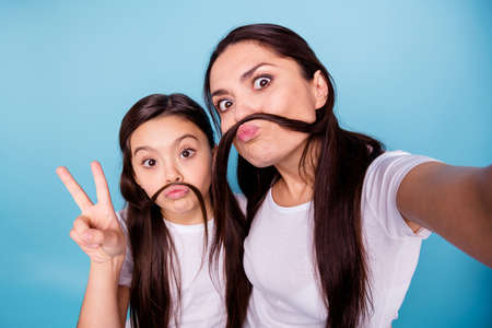 Foto de Close up photo beautiful two people brown haired mom small little daughter make take selfies moustache curls pretend guy man male show v-sign wear white t-shirts isolated bright blue background - Imagen libre de derechos
