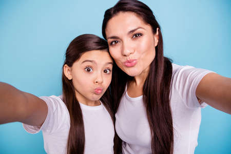 Photo for Close up photo cheer two people brown haired mum mom small little daughter make take selfies mouth lips in form shape figure ducky kissing wear white t-shirts isolated bright blue background - Royalty Free Image