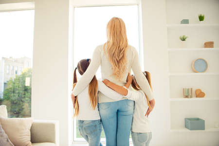 Photo for Rear back behind view of nice stylish trendy slim people mom mum girls hugging in front of window in light white interior room hotel indoors - Royalty Free Image