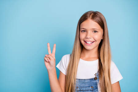 Foto de Close-up portrait of her she nice cute lovely sweet charming winsome attractive cheerful cheery straight-haired blonde pre-teen girl showing v-sign isolated on blue pastel background - Imagen libre de derechos
