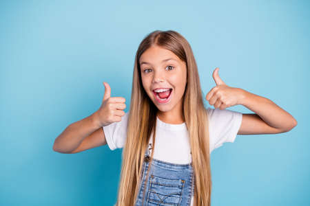 Photo for Close-up portrait of her she nice cute adorable lovely sweet attractive cheerful cheery straight-haired blonde pre-teen girl opened mouth showing thumbup isolated on blue pastel background - Royalty Free Image