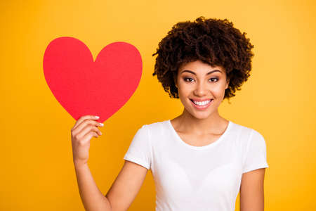 Foto per Close up photo beautiful amazing she her dark skin lady showing big paper card heart shape figure form lovely date invitation wear casual white t-shirt isolated yellow bright vibrant background - Immagine Royalty Free