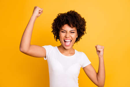 Foto de Close up photo beautiful amazing she her dark skin lady yelling loud glad hands arms fists raised great big win competition wear casual white t-shirt isolated yellow bright vibrant vivid background - Imagen libre de derechos