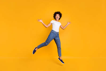 Foto de Full length body size photo jumping high beautiful she her lady like comedian actor playful active energetic wearing casual jeans denim white t-shirt clothes isolated yellow background - Imagen libre de derechos