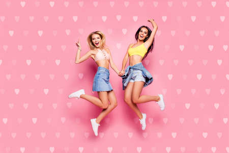 Foto de Life is cool Full length body size view of beautiful attractive funny cheerful careless girls in casual trendy outfit white shoes jumping up holding hands isolated on pastel pink background - Imagen libre de derechos