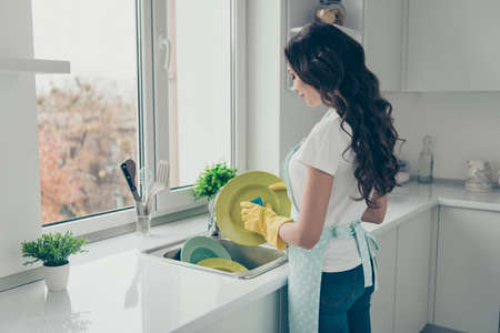 Photo pour Profile side view portrait of her she nice charming lovely attractive beautiful cheerful wavy-haired house-wife washing green plates in yellow gloves in modern light white interior - image libre de droit