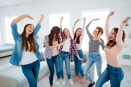 Photo for Nice-looking lovely cool charming attractive cheerful glad careless carefree dreamy optimistic girls wearing casual raising hands up rejoicing having fun in light white interior room house indoors - Royalty Free Image