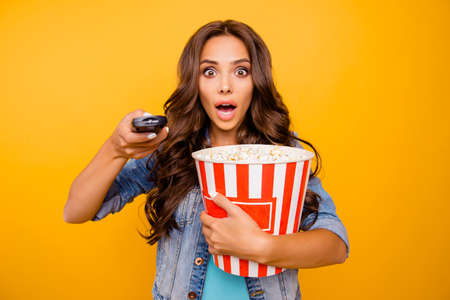 Foto de Close up photo beautiful her she lady yell scream shout hold big large popcorn box stupor staring change channel wear blue teal green short dress jeans denim jacket clothes isolated yellow background - Imagen libre de derechos