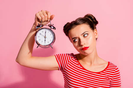 Photo pour Close-up portrait of her she nice cute charming attractive glamorous sad teen girl wearing striped t-shirt holding in hand showing clock boring hour isolated over pink pastel background - image libre de droit