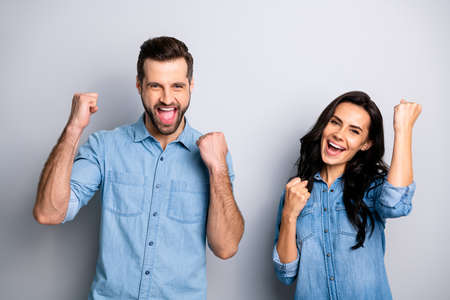 Foto de Yeah Hooray Portrait of yelling excited person students delighted impressed about their luck in lottery raising fists wearing blue denim clothing isolated on argent background - Imagen libre de derechos