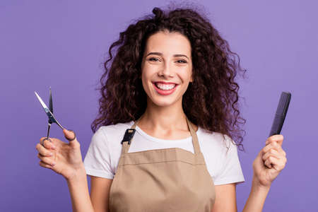 Photo pour Close up photo pretty beautiful her she lady hold hands arms haircut equipment sincerely toothy smiling guests clients customers wear casual white t-shirt apron isolated violet purple background - image libre de droit