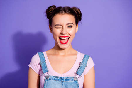 Foto de Close up photo beautiful amazing she her lady two buns open mouth wink boys guys cheerful pretty red lips pomade wear casual t-shirt jeans denim overalls clothes isolated purple violet background - Imagen libre de derechos