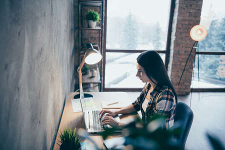 Foto de Above high angle profile side view of her she nice charming executive manager director brunette lady wearing checked shirt typing report at industrial loft style interior room work place station - Imagen libre de derechos