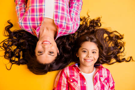 Foto de Close up top above high angle view photo beautiful she her models mom daughter adorable amazing long hair weekend lying floor wear casual pink plaid checkered shirts isolated yellow background - Imagen libre de derechos