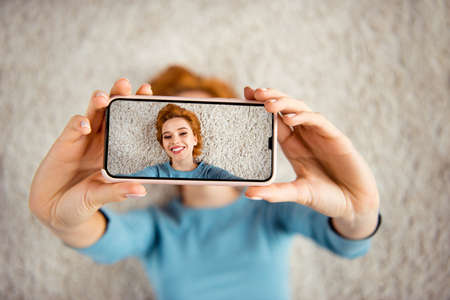 Photo pour Close up photo amazing beautiful she her lady hands telephone make take selfies toothy smile adorable vacation days wear blue pullover clothes lying carpet floor divan house loft living room indoors - image libre de droit