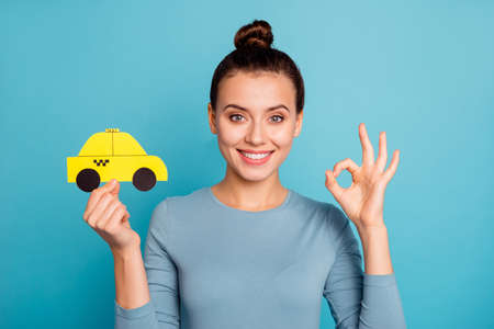 Photo pour Close up photo top-knot positive satisfied cheerful hipster advertise choose advert feedback hold hand paper card yellow taxi car cab route trendy stylish beautiful shirt isolated blue background - image libre de droit