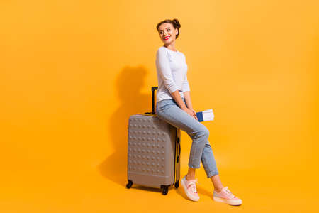 Foto de Profile side full length body size photo of cute charming youngster in light denim clothes standing in queue for her jet sitting on trolley bag holding documents on vivid background - Imagen libre de derechos