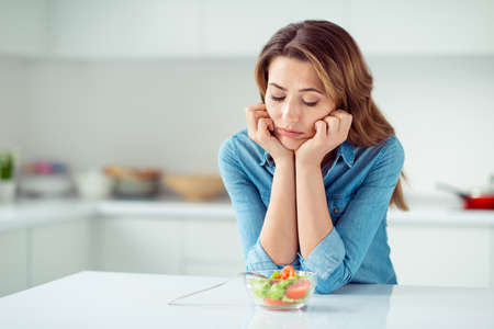 Foto de Close-up portrait of her she nice lovely charming attractive sad bored dull disappointed brown-haired lady looking at new green detox vitamin salad in light white interior style kitchen - Imagen libre de derechos