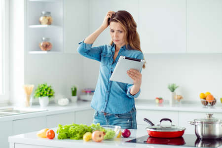 Foto de Portrait of her she nice lovely attractive confused brown-haired lady thinking how to prepare fresh hot dish meal dinner lunch green eco delicacy in light white interior style kitchen - Imagen libre de derechos