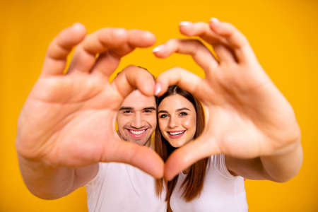 Photo pour Close up photo amazing she her he him his guy lady hands arms fingers make heart figure faces inside form married spouse romance mood wear casual white t-shirts outfit isolated yellow background - image libre de droit
