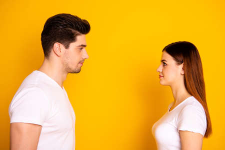 Foto de Close up side profile photo funny beautiful she her he him his guy lady stand opposite wait first who take eyes off each other lovely look wear casual white t-shirts outfit isolated yellow background - Imagen libre de derechos