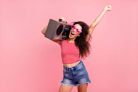 Photo pour Portrait of her she nice attractive lovely cool charming cheerful cheery crazy ecstatic wavy-haired lady carrying player event night club clubber isolated over pink pastel background - image libre de droit