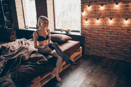 Photo for Nice-looking gorgeous attractive winsome luxury elegant slim fit thin feminine lady sitting on bed putting pantyhose off in loft brick industrial style interior room house indoors - Royalty Free Image