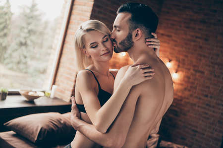 Foto de Profile side view portrait of nice charming attractive gorgeous stunning lovely lovable lady cuddling masculine macho guy harmony idyllic affair in loft brick industrial style interior room house - Imagen libre de derechos