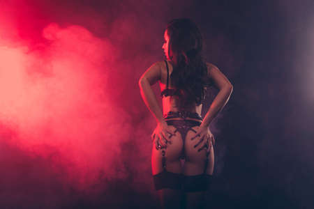 Photo pour Rear back behind view of attractive stunning sportive perfect muscular fit thin shape form line wavy-haired lady wearing swordbelt teasing holding in hands bum isolated on red light black background - image libre de droit