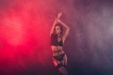 Photo for Nice attractive fascinating charming sportive perfect figure wavy-haired lady wearing swordbelt teasing posing closed eyes enjoying lifestyle night club clubber isolated on red light black background - Royalty Free Image