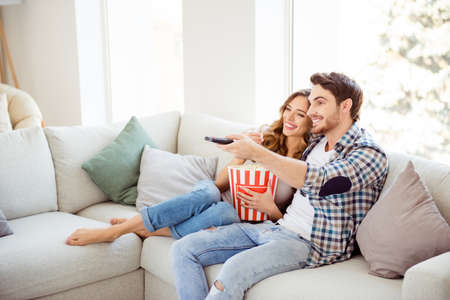 Photo pour Profile side view of his he her she two person nice attractive charming cheerful guy lady sitting on divan watching new drama comedy in light white style interior living room hotel house indoors - image libre de droit